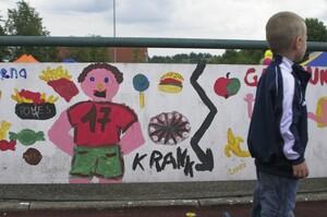 Falsche Ernährung und mangelnde Bewegung kann krank machen, warnt dieses Kinder-Graffiti an einem Sportplatz. Foto: picture-alliance