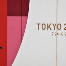 Eine Frau mit Mundschutz schaut auf ihre Smartphone. Im Hintergrund ist ein Tokio 2020 Plakat.