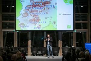 Sportmanager Michael Mronz präsentiert 2019 in Berlin eine Grafik, die zeigt, an welchen Orten olympische Wettkampfstätten im Rahmen von Olympia an Rhein-Ruhr im Jahre 2032 liegen sollen. Foto: picture-alliance