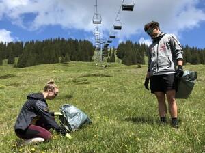 Die Snowboarder Lilith Kuhnert und Paul Berg sammeln unter dem Sessellift am Grasgehren Müll. Foto: Snowboard Germany