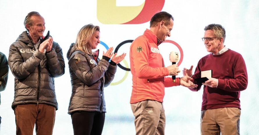 Medaille für den Minister: Der Deutsche Botschafter Stephan Auer und seine Frau Vera Auer applaudieren Bundesinnenminister Thomas de Maizière, den DOSB-Präsident Alfons Hörmann auszeichnet (Foto: Picture Alliance)