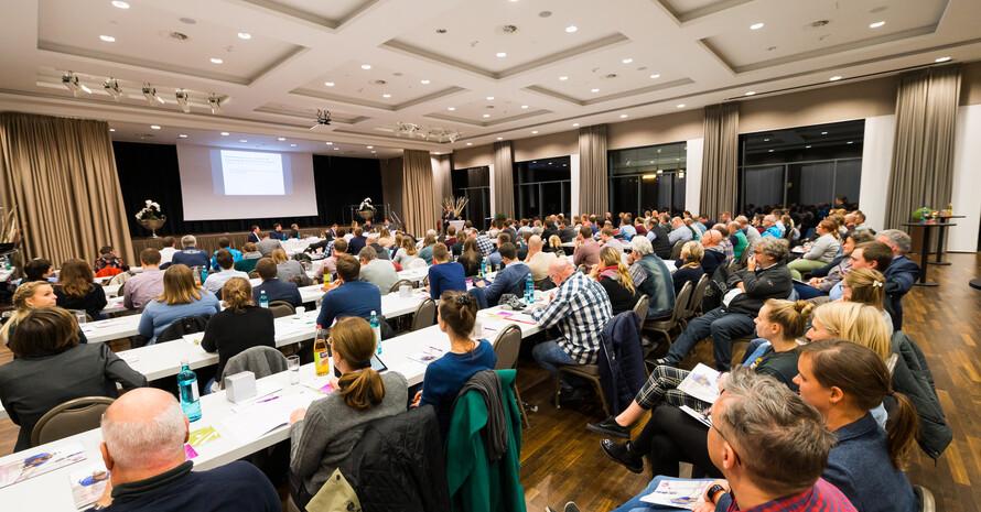 Blick in einen Veranstaltungssaal. Viele Menschen sitzen in Stuhlreihen an Tischen und hören einer Präsentation zu.