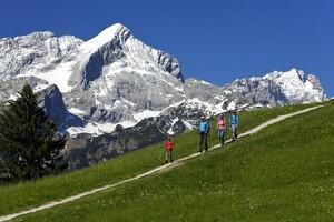 Wanderer auf dem Eckbauer mit Blick zur Alpspitze und Zugspitze bei Garmisch-Partenkirchen in Bayern. Foto: picture-alliance