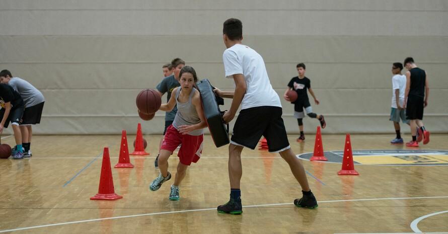 Ein junger Trainer motiviert Kinder beim Basketballtraining. Foto: picture-alliance