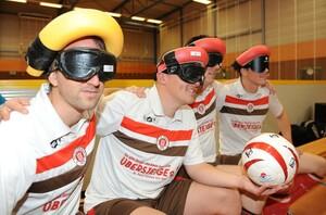 Vier Menschen sitzen nebeneinander auf einer Bank in einer Sporthalle. Sie tragen eine blickdichte Brille und einen Kopfschutz. Eine Person hält einen Fußball in der Hand. Sie haben Trikots des FC St. Pauli an.