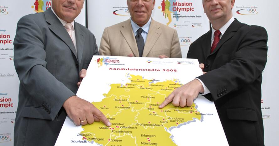 Jury-Mitglieder präsentieren eine Deutschlandkarte mit allen Kandidatenstädten: Vlnr: Walter Schneeloch, Vize-Präsident des DOSB., Dr. Peter Danckert, MdB und Vorsitzender des Sportausschusses im Deutschen Bundestag, Uwe Kleinert,  Leiter Corporate Responsibility, Coca-Cola GmbH.