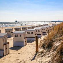 Ein Strand mit Strandkörben und Blick auf das Meer und eine Seebrücke.