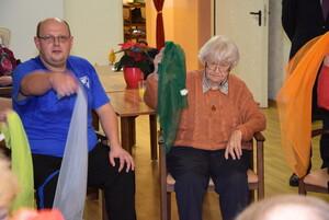 Zwei Personen sitzen jeweils auf einem Stuhl und bewegen ein Tuch, welches sie in der rechten Hand halten.