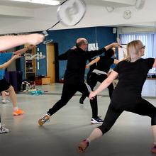 Viele Badminton-Spieler simulieren in einer Halle vor einem großen Spiegel die Schläge.