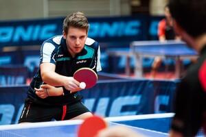Frédéric Peschke beim Tischtennis. Er hält den Schläger in der rechten Hand und spielt gerade einen Ball. Den linken Arm hat er mit einer Manschette am Körper angelegt.