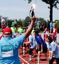 Ein Kampfrichter gibt den Startschuss zu einem Vorlauf bei den Special Olympics, den nationalen Sommerspielen für Menschen mit geistiger oder mehrfacher Behinderung. Einige Menschen stehen an der Startlinie, viele weitere feuern als Zuschauer*innen an.
