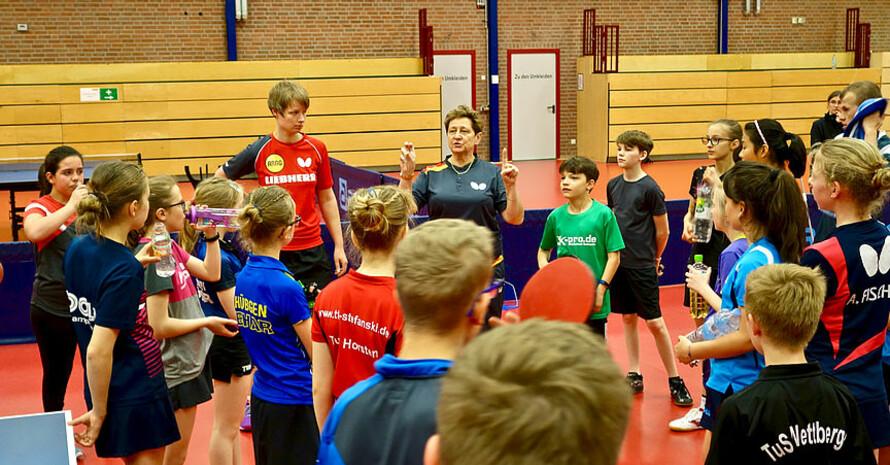 Eine Trainerin erklärt etwas mit Handzeichen. Eine andere Trainerin steht daneben. Eine Gruppe mit Jungen und Mädchen hört und schaut zu.