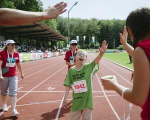 """Was könnte den Slogan auf dem T-Shirt von Julius Purschke vom LLC Marathon Regensburg - """"Was wir alleine nicht schaffen...""""  - besser vollenden als die Botschaft dieses Fotos?  Aufgenommen beim 100-m-Lauf  bei den Special Olympics Düsseldorf 2014. Julius Purschke kam mit drei Sekunden Rückstand auf den Dritten ins Ziel, getragen vom Beifall der Zuschauer und gefeiert von den Helfern. Foto: SOD/Jörg Brüggemann (OSTKREUZ)"""