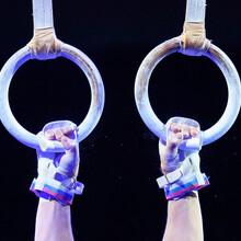 Schwarzer Hintergrund, Ringe beim Turnen in der Bildmitte mit zwei Händen, die sie greifen.
