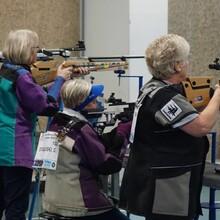 Es sind fünf Damen zu sehen, die mit einem Luftgewehr in den Händen stehend und z.T. sitzend das Ziel anvisieren.