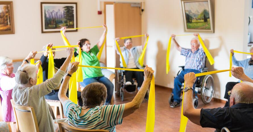 Menschen sitzen in einer Pflegeeinrichtungen im Stuhlkreis und machen Übungen mit Therabändern.