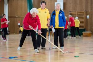 Das Bild zeigt eine Sporthalle. Im Vordergrund schauen zwei Personen, eine mit Krücke, einer dritten Person beim Ausführen einer Sportdisziplin zu.