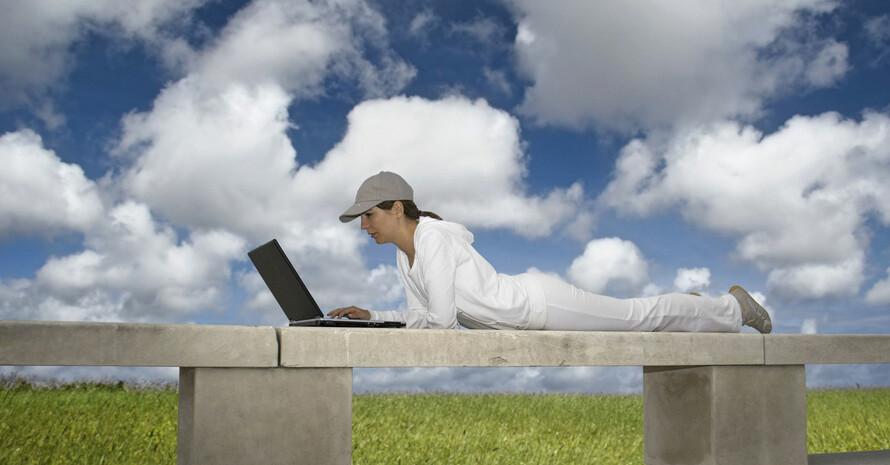 Frau liegt mit einem Laptop auf einer Mauer. Foto: picture-alliance