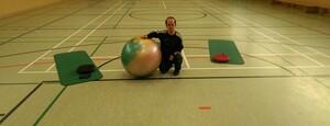Ingo Giewolies in einer Sporthalle. Sein rechter Arm liegt auf einem großen bunten Gymnastikball.