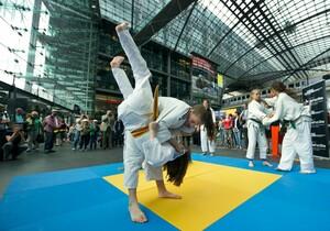 Judo-Kämpferinnen demonstrieren am Berliner Hauptbahnhof vor staunenden Passanten ihr Können. Foto: Camera4