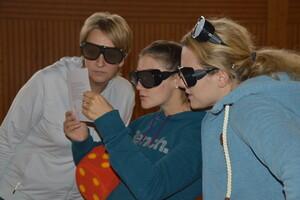 Drei Frauen mit Simulationsbrillen lesen etwas auf einem Papier, was die Frau in der Mitte in den Händen hält.