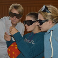 Drei Frauen mit Simulationsbrillen lesen etwas auf einem Papier, was die Frau in der Mitte in den Händen hält. Sie hat auch einen Schaumstoffwürfel unter dem Arm.