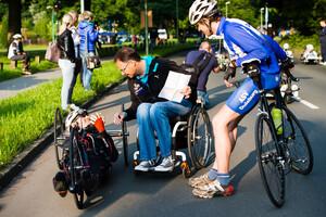 Eine Person auf dem Handbike, eine Person im Rollstuhl und eine Person, die an der Mittelstange ihres Fahrrads gelehnt steht. Die Person im Rollstuhl hat ein weißes Papier in der Hand und spricht mit der Person im Handbike.