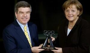 Bundeskanzlerin Angela Merkel freut sich über die IOC-Auszeichnung, die sie aus den Händen von DOSB-Präsident Thomas Bach im Berliner Kanzleramt entgegen nimmt - stellvertretend für das faire Publikum bei den Weltmeisterschaften in Deutschland 2007. Foto: camera4
