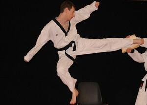 Marcel Dirmeier bei einer Taekwondo-Übung. Er tritt im Sprung mit einem Fuß gegen ein Brett, das eine andere Person hält.