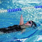 Vera Thamm beim Rückenschwimmen mit schwarzer Kappe und Schwimmbrille. Ihre Arme sind verkürzt.