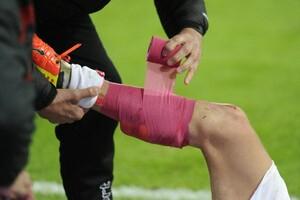 Verletzung auf dem Spielfeld: Der Unterschenkel eines Fußballspielers wird bandagiert. Foto: picture-alliance