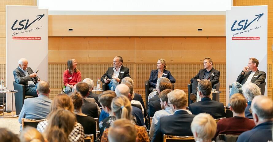 Auf dem Podium sitzen sechs Personen, darunter zwei Frauen. Rechts und links steht jeweils ein Roll-Up mit dem Logo des LSV Schleswig-Holstein. Zuschauerinnen und Zuschauer sind von hinten zu sehen.