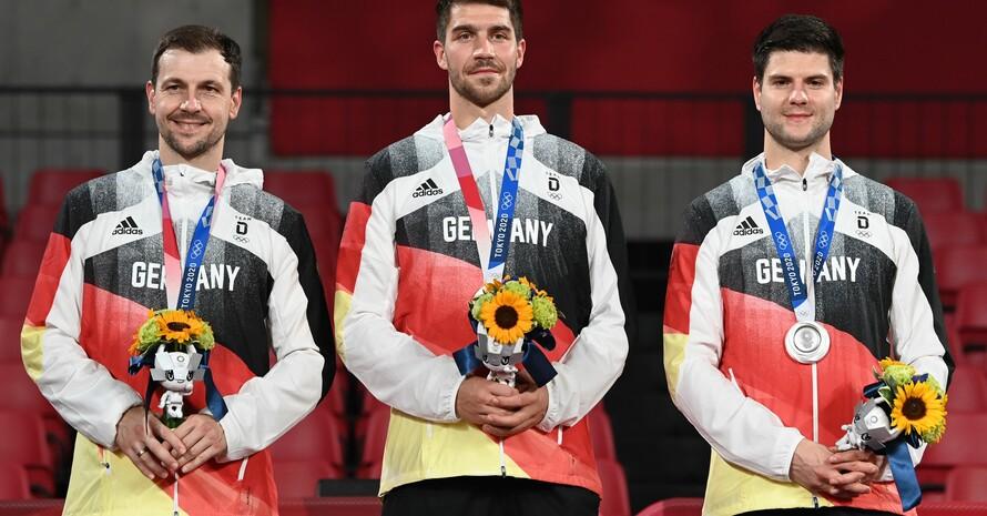 Vom ersten Ärger der deutschen Tischtennis-Männer über das klar verlorene Finale gegen China war bei der Siegerehrung nichts mehr zu sehen (v.li.): Boll, Franziska, Ovtcharov; Foto: picture-alliance