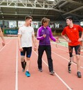 Drei Sportler mit einer Beinprothese und ihre Trainerin gehen auf einer Laufbahn. Die Trainerin erklärt etwas.