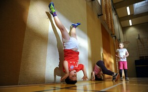 Schülerinnen und Schüler der zweiten Klasse üben in einer Turnhalle den Kopfstand. Foto: picture-alliance