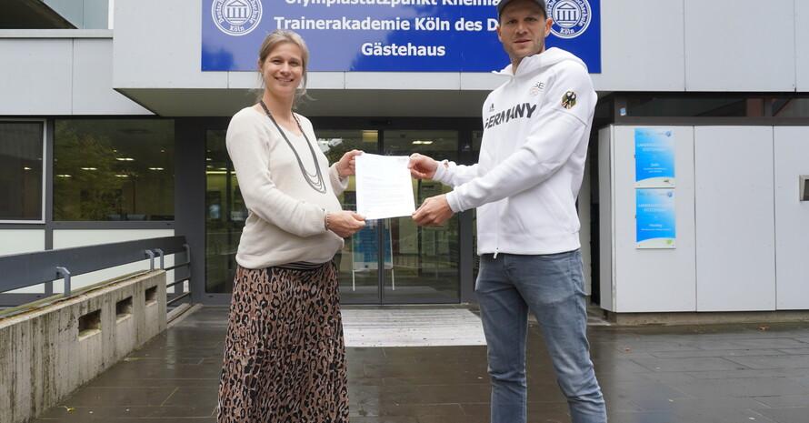 IOC-Athletensprecherin und DOSB-Präsidiumsmitglied Britta Heidemann übergibt Kanute Max Hoff das Schreiben über die Zusage seines IOC-Stipendiums. Beide stehen draußen auf einer Treppe vor dem Olympiastützpunkt Rheinland.