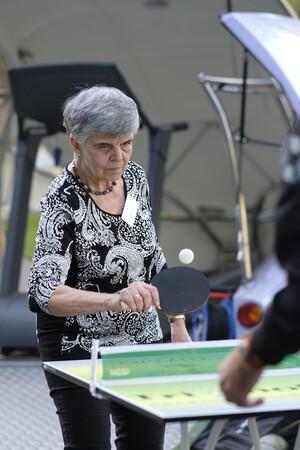 Ältere Frau mit grauen Haaren führt konzentriert den Tischtennisschläger