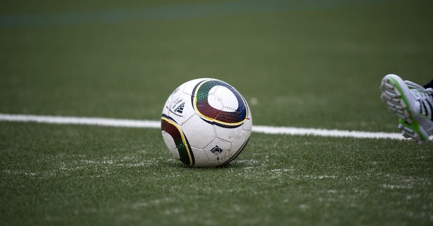 Ein Fußball liegt auf einem Fußballfeld. Am rechten Bildrand ist der Fuß eines Spielers oder einer Spielerin zu sehen, die einen Fußballschuh trägt.