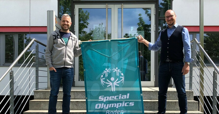 Eine Person steht rechts und eine Person steht links neben einer Fahne. Sie halten diese fest. Auf der Fahne steht Special Olympics Baden-Württemberg. Sie stehen auf einer Treppe vor einem Gebäude.