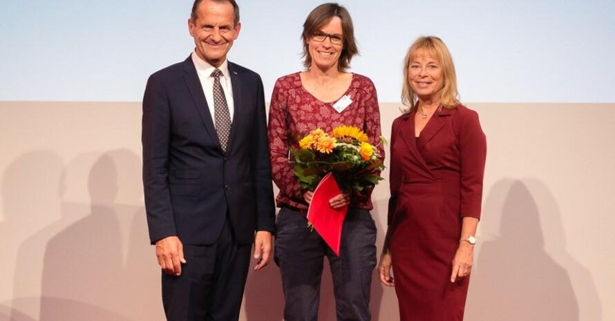Jutta Heeß (mitte) wurde für ihre langjährige Berichterstattung über und für Frauen im Sport von Alfons Hörmann (links) und Petra Tzschoppe (rechts) geehrt. Foto: Foto: bewahredieZeit/DOSB
