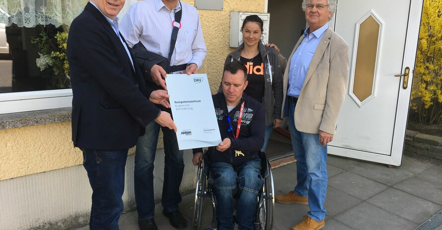"""Das Bild zeigt fünf Personen, eine davon sitzt im Rollstuhl. Sie stehen vor einem Haus und halten eine Tafel mit der Aufschrift """"Kompetenzzentrum Rudern mit Behinderung"""" in den Händen."""