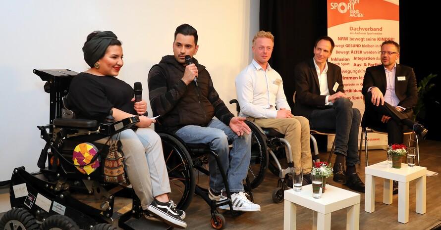 Auf einer Bühne sitzen sechs Personen und diskutieren. Drei davon sitzen in einem Rollstuhl.