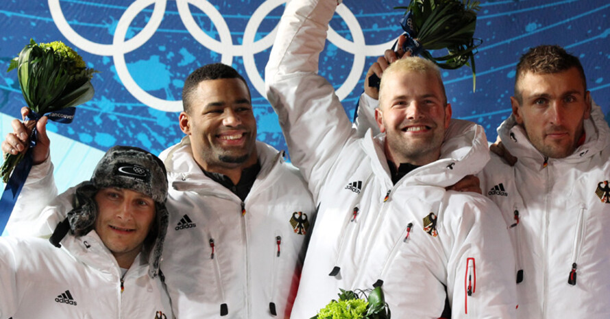 Thomas Florschütz, Richard Adjei, André Lange und Kevin Kuske (v.l.) freuen sich über den Doppel-Olympiasieg. Copyright: picture-alliance