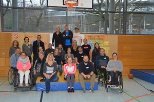 Gruppenbild der Teilnehmer/innen in der Turnhalle. Einige Personen sitzen im Rollstuhl.