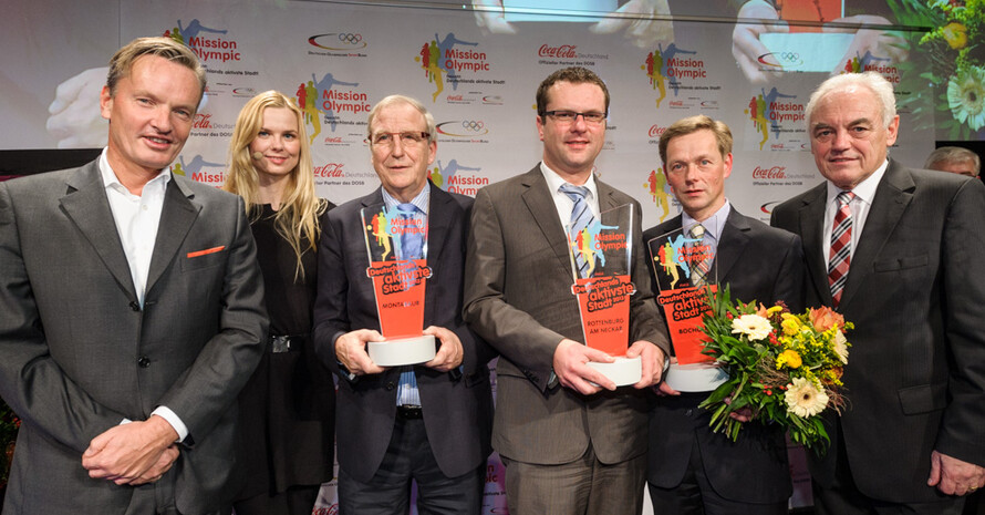 Schwimmstar Britta Steffen, Walter Schneeloch vom DOSB (re.) und Hendrik Steckhan von Coca-Cola (li.) gratulieren den Repräsentanten der Siegerstädte . Foto: Wagenzik