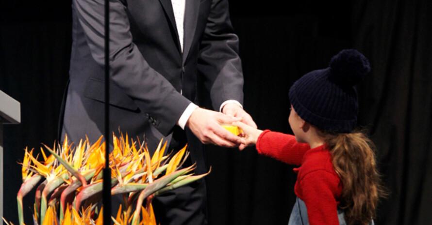 Die kleine Stella überreicht Bundespräsident Wulff ein Kaleidoskop. Foto: picture-alliance