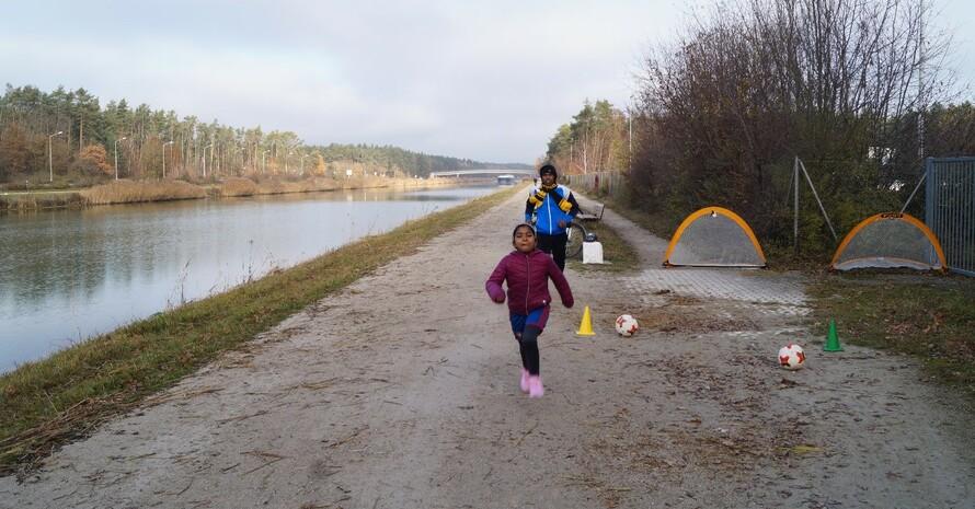 Vater und Tochter laufen gemeinsam bei Sonnenschein am Rhein-Main-Donaukanal
