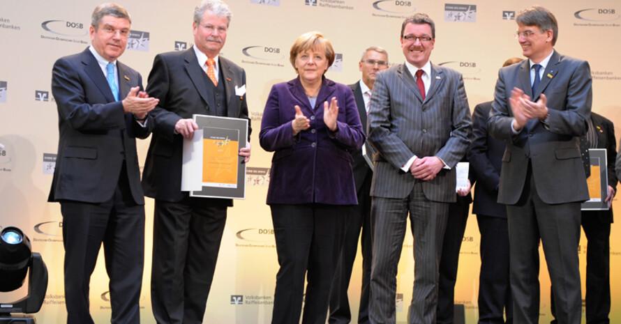 DOSB-Präsident Thomas Bach,Werner Müller von der Sportgemeinschaft Marßel, Bundeskanzlerin Angela Merkel, Hartmut Schulz von der Volksbank Bremen-Nord und BVR-Präsident Uwe Fröhlich (v.l.) bei der Preisverleihung in Berlin. Foto: Sterne des Sports