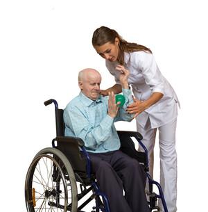 Ein älterer Mann sitzt in einem Rollstuhl und bewegt einen Massageball zwischen dem einen Arm und der anderen Hand. Eine Frau in weißer Kleidung unterstützt ihn dabei.