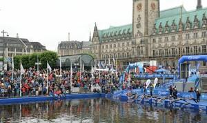 Das Starterfeld springt 2015 bei der Mixed Team WM beim Triathlon in Hamburg vor dem Rathaus in die Alster. Foto: picture-alliance